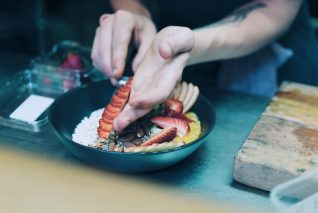 A chef plating a brunch bowl